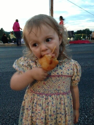 little girl eating corndog