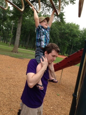 dad helping little boy on monkey bars