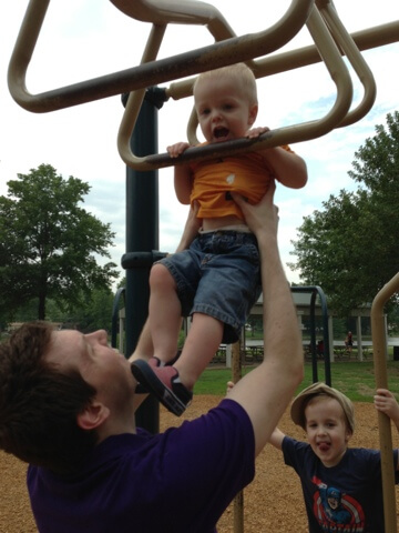 daddy helping toddler with monkey bars