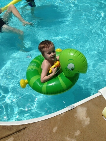 boy floating with inner tube in pool