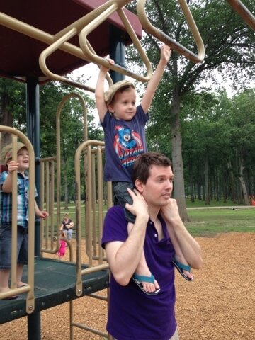 dad helping boy on monkey bars
