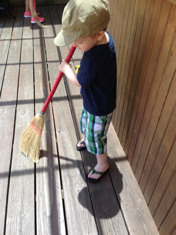 young boy using broom