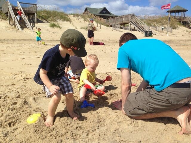 boys making sand castles with dad