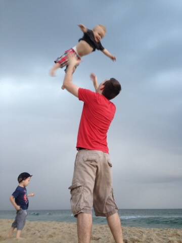dad tossing toddler boy in the air