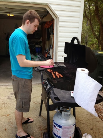 man grilling hot dogs