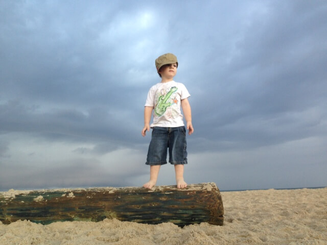 young boy standing on log