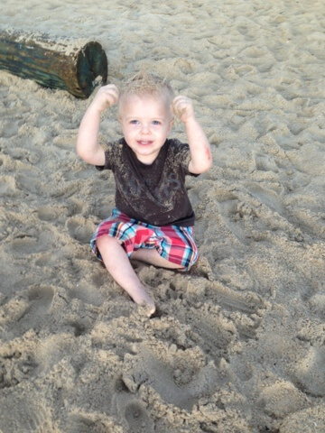toddler boy covered in sand