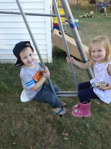 little boy and girl on swing