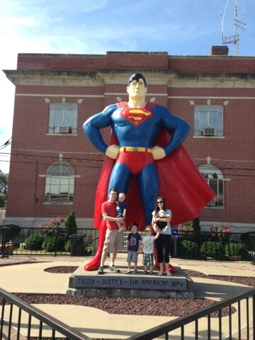 big family and giant superman statue