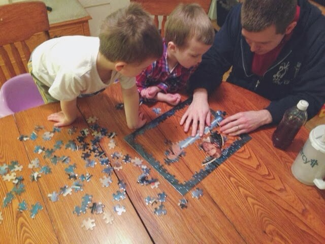 dad and boys working on puzzle