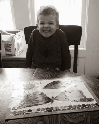 little boy with finished puzzle