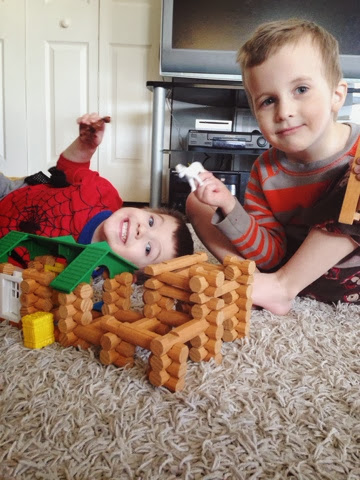 boys playing with lincoln logs