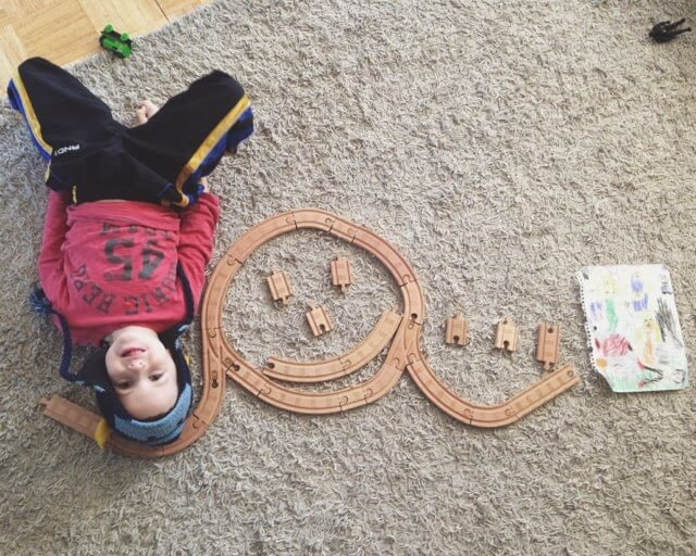 boy made happy face out of toy train tracks