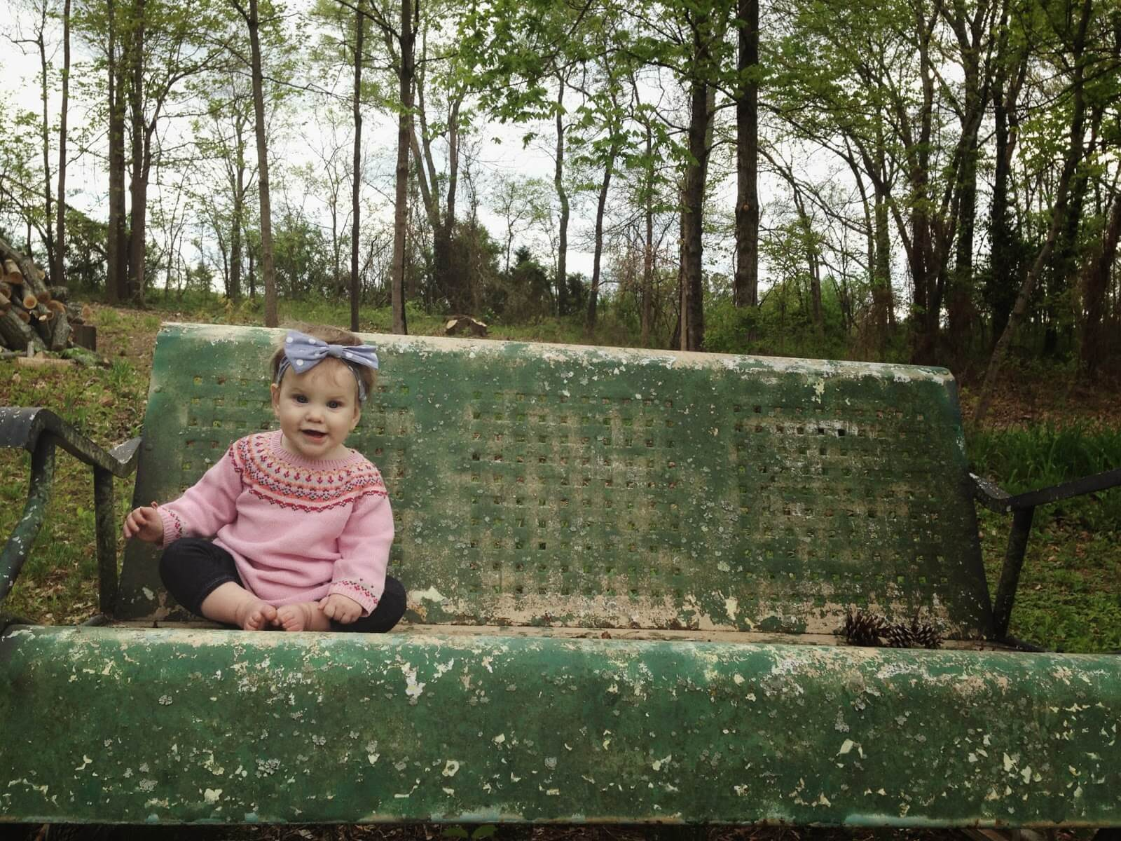 cute baby girl sitting on bench