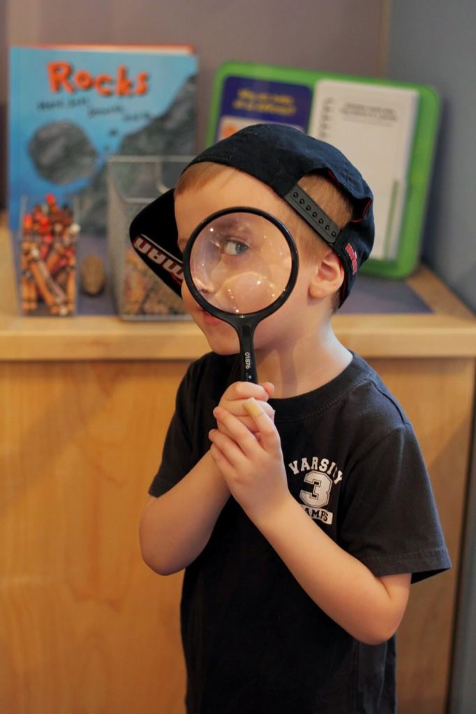 boy holding magnifying glass over eye