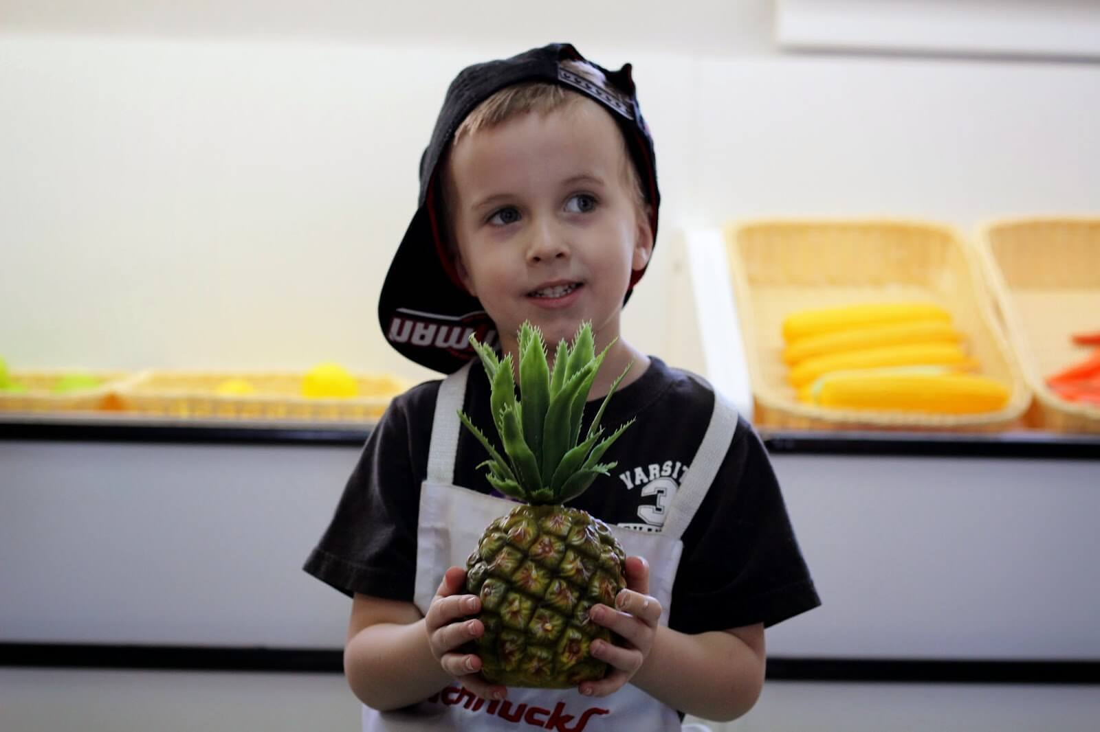 boy holding pineapple