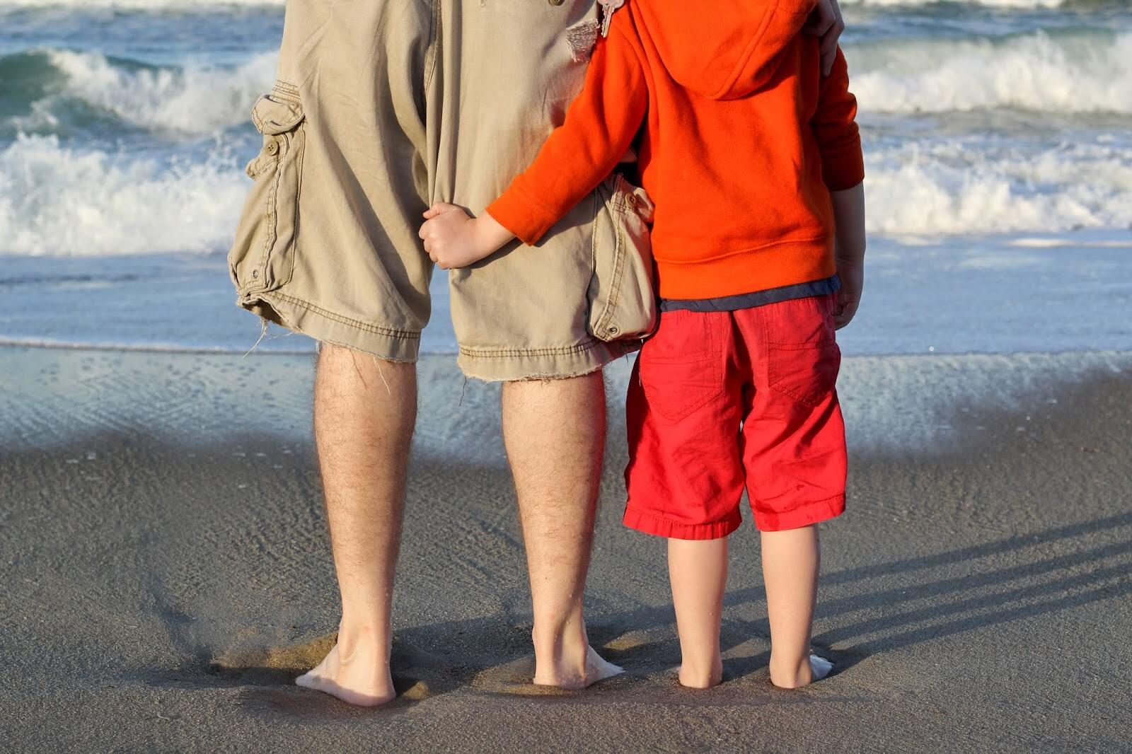 dad and boy on beach feet in sand