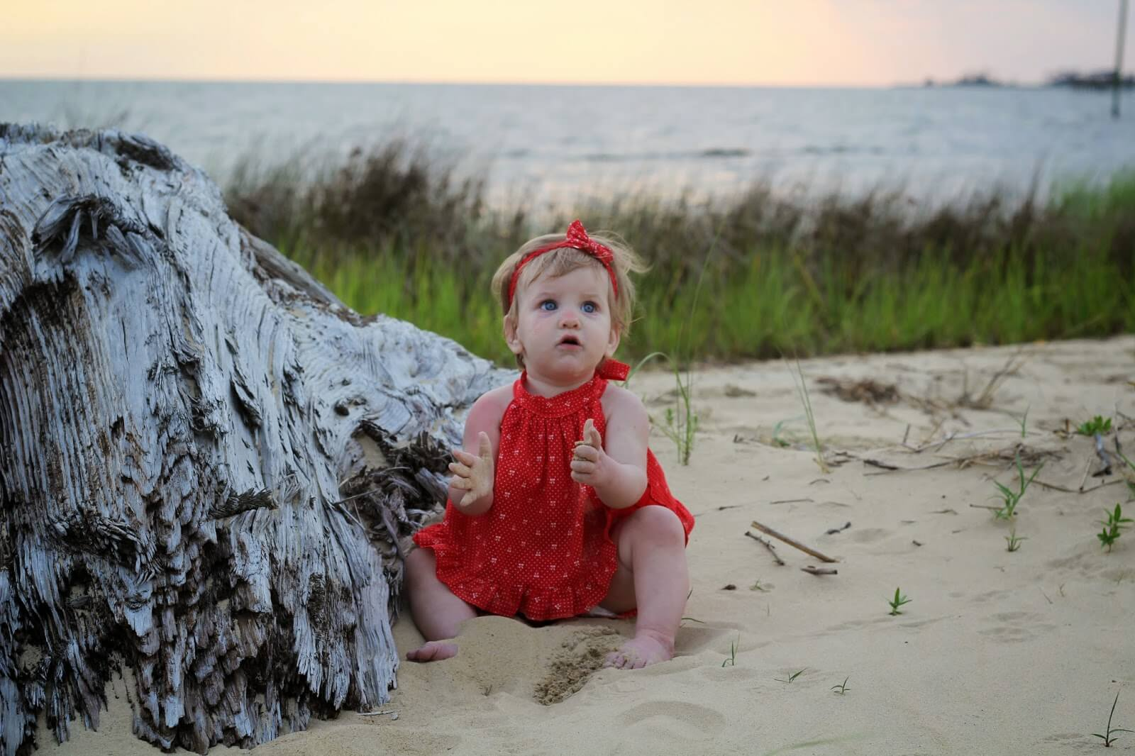 cute baby girl sitting in sand