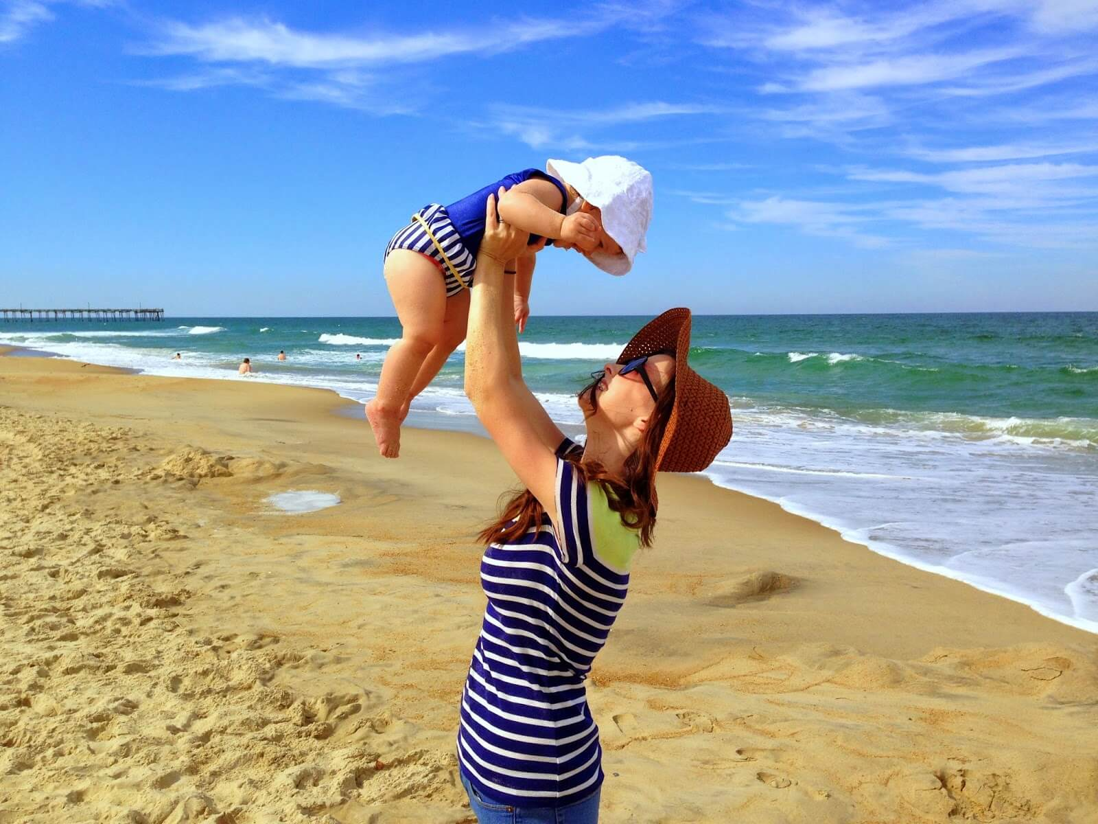 young mom holding baby in the air