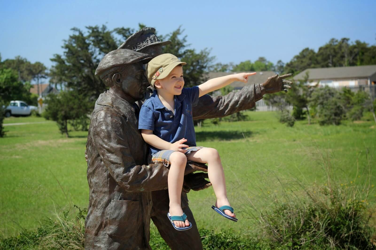 little boy posing with statue