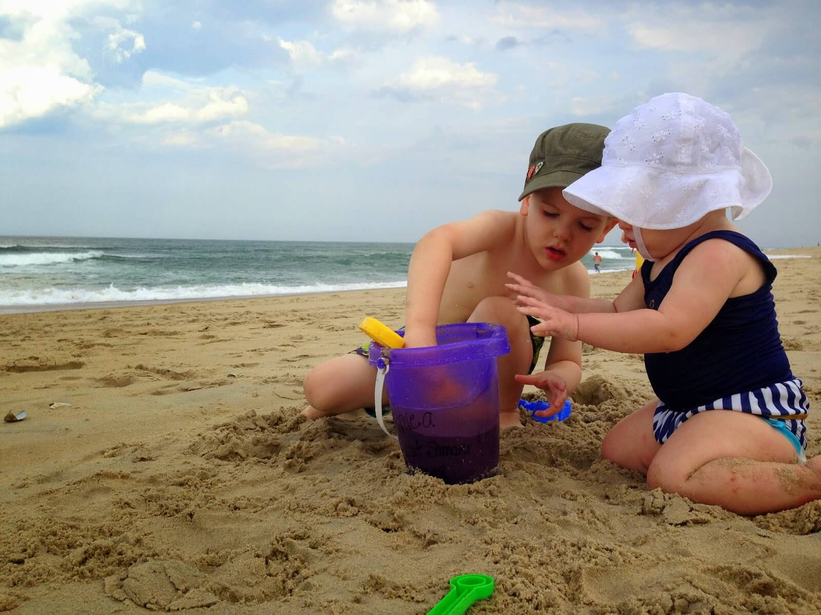 little boy and baby girl playing in sand