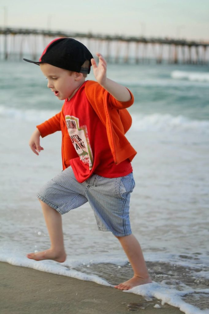 boy running from ocean waves