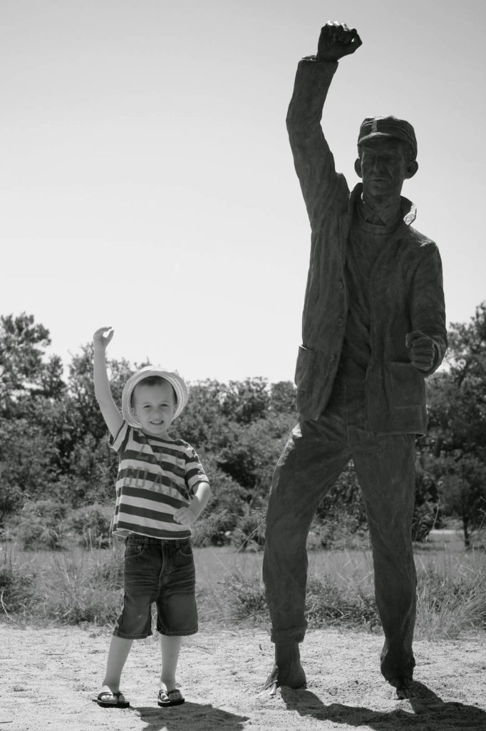 boy posing with statue
