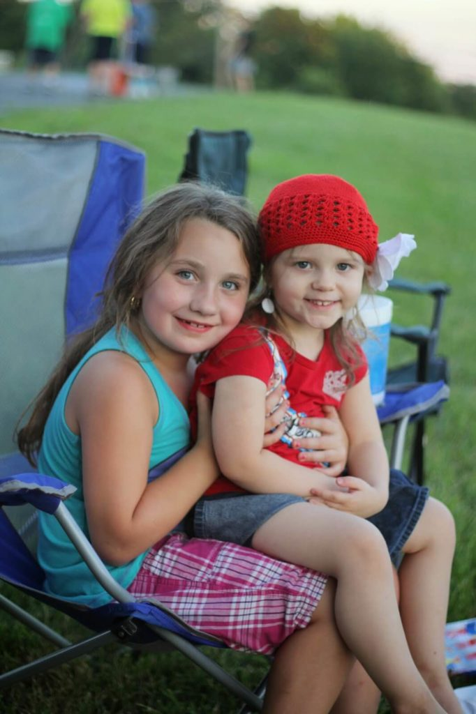 two girls sitting on lawn chair