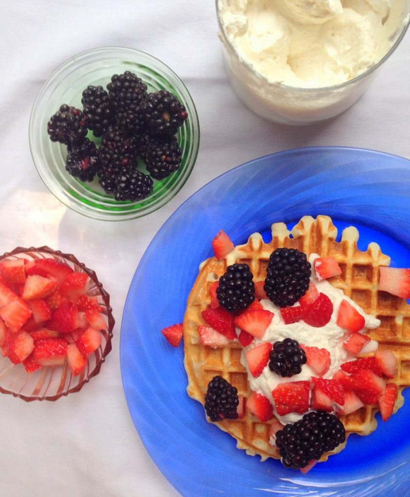 waffle with fruit topping and whipped cream