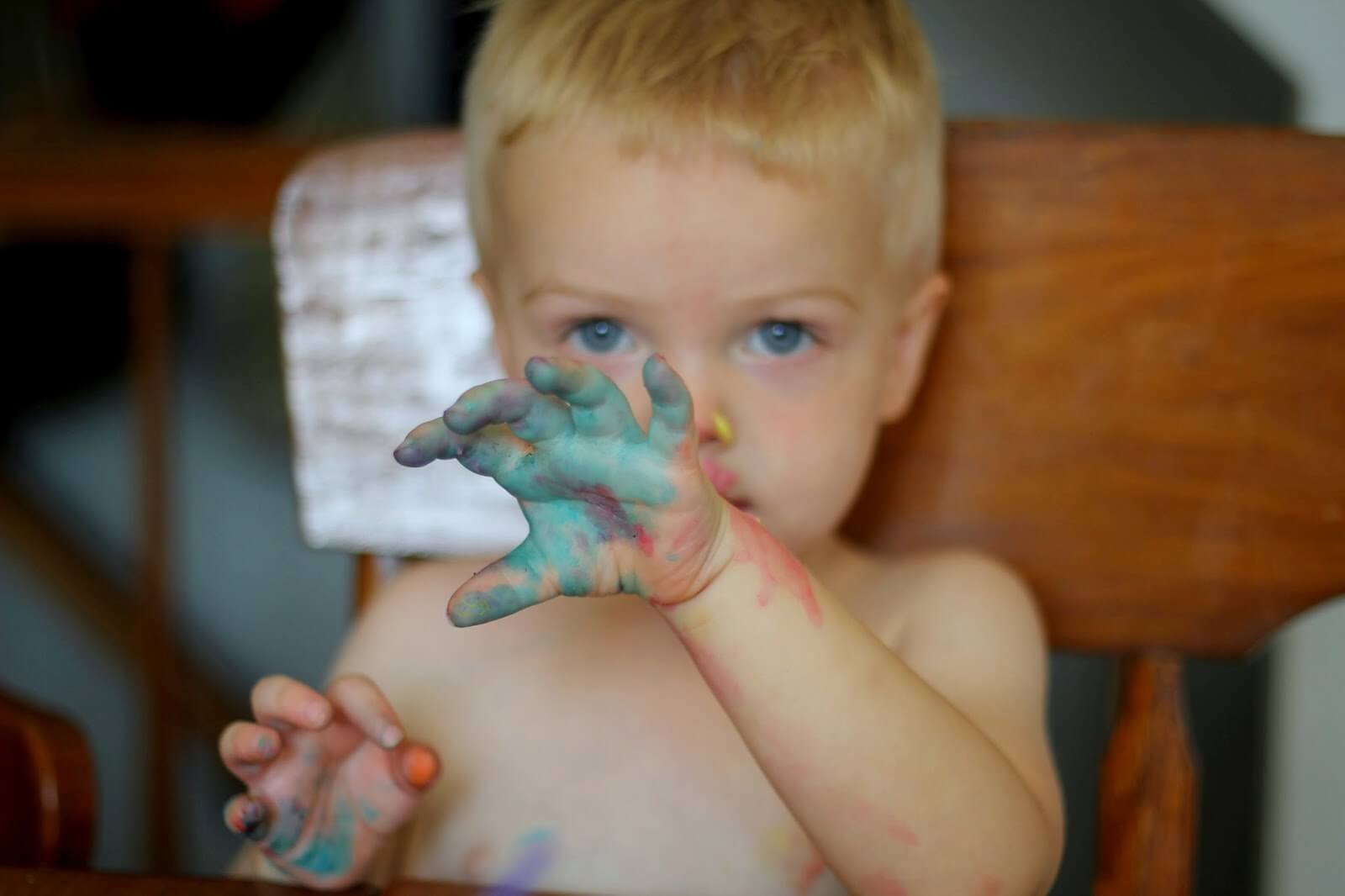 toddler boy with paint on hands