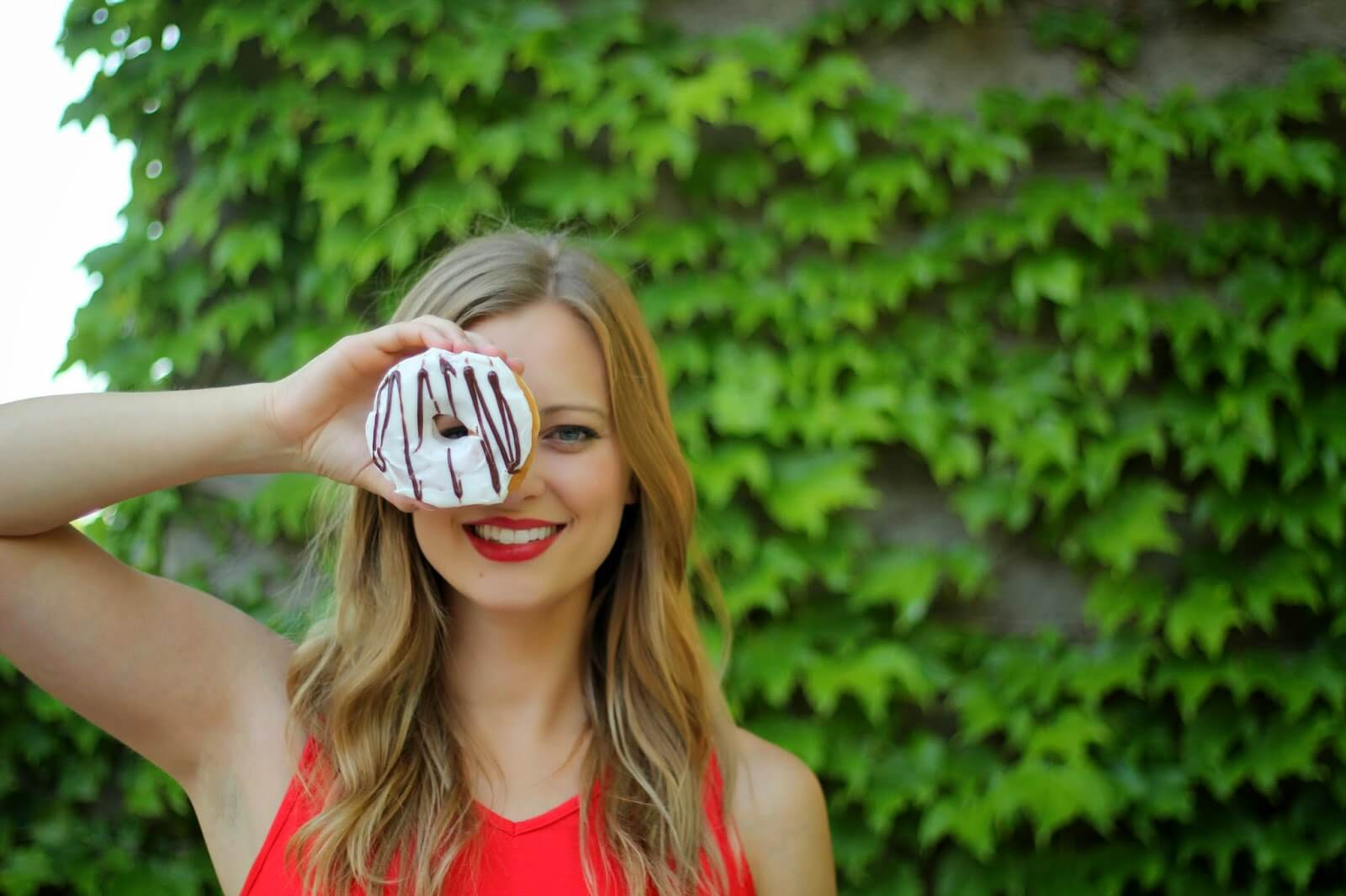 woman holding donut over eye