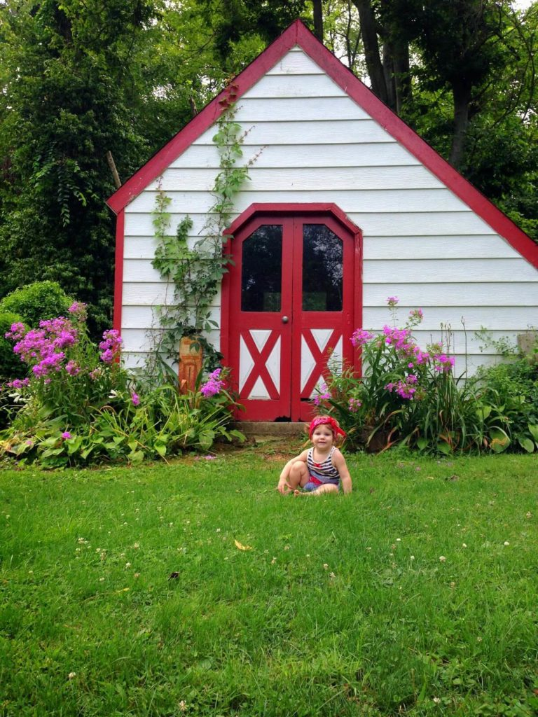 cute baby sitting by red and white shed