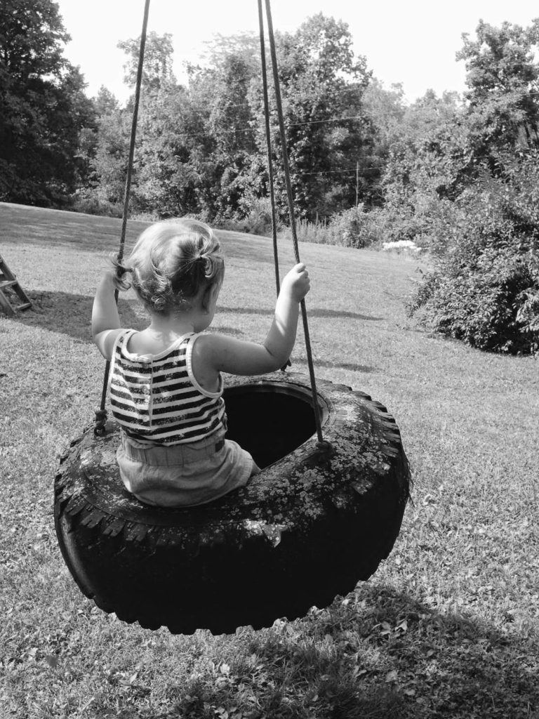 black and white picture of girl on tree swing