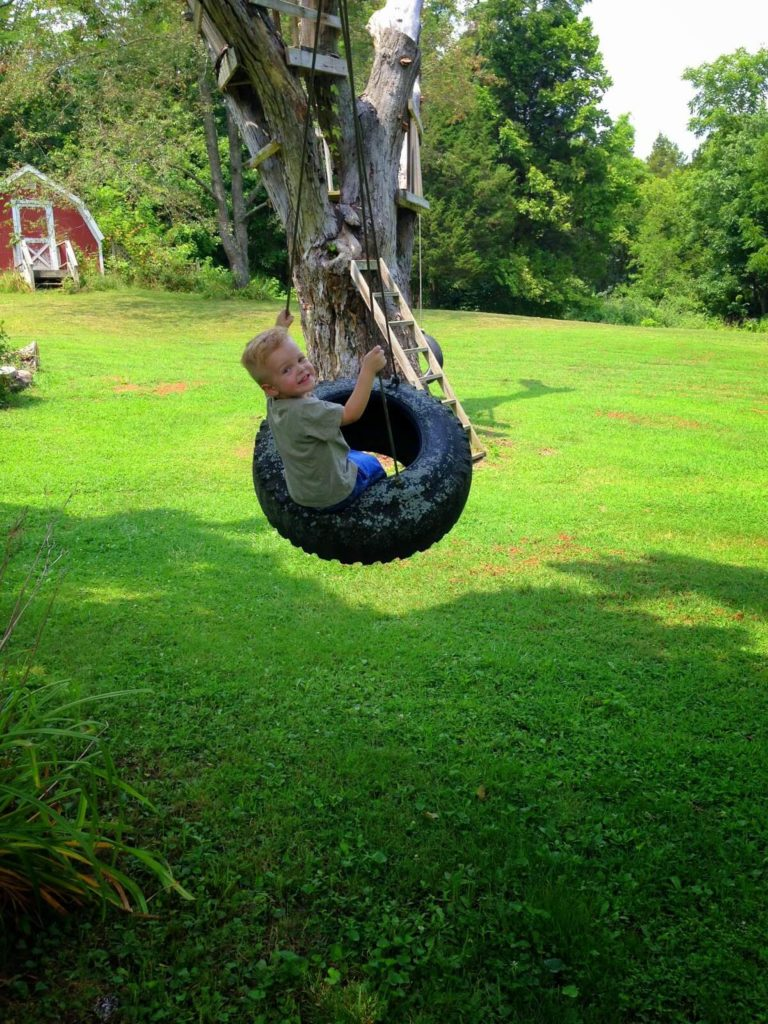 toddler swinging on tire swing