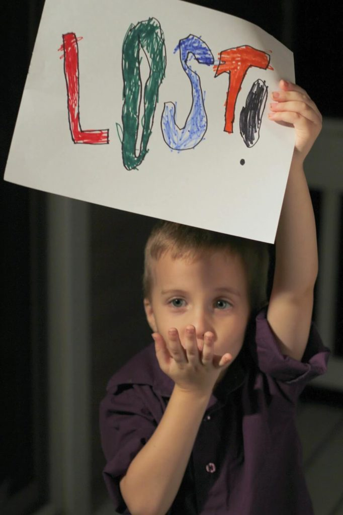 boy holding lost sign