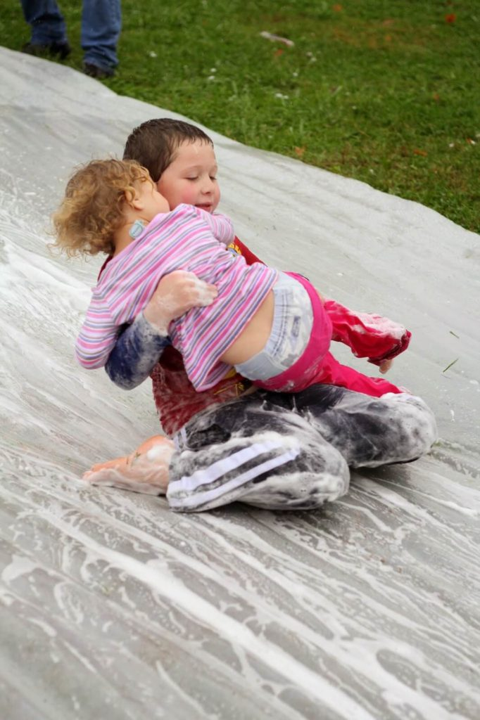 boy and girl sliding down soapy water slide
