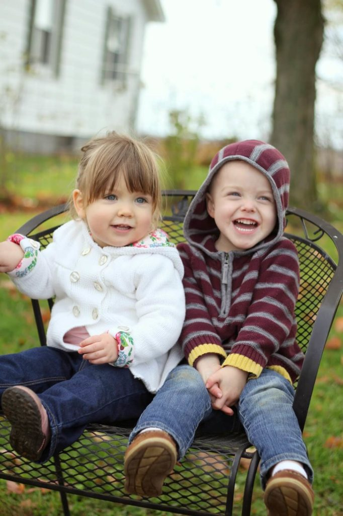 boy and girl sitting on chair
