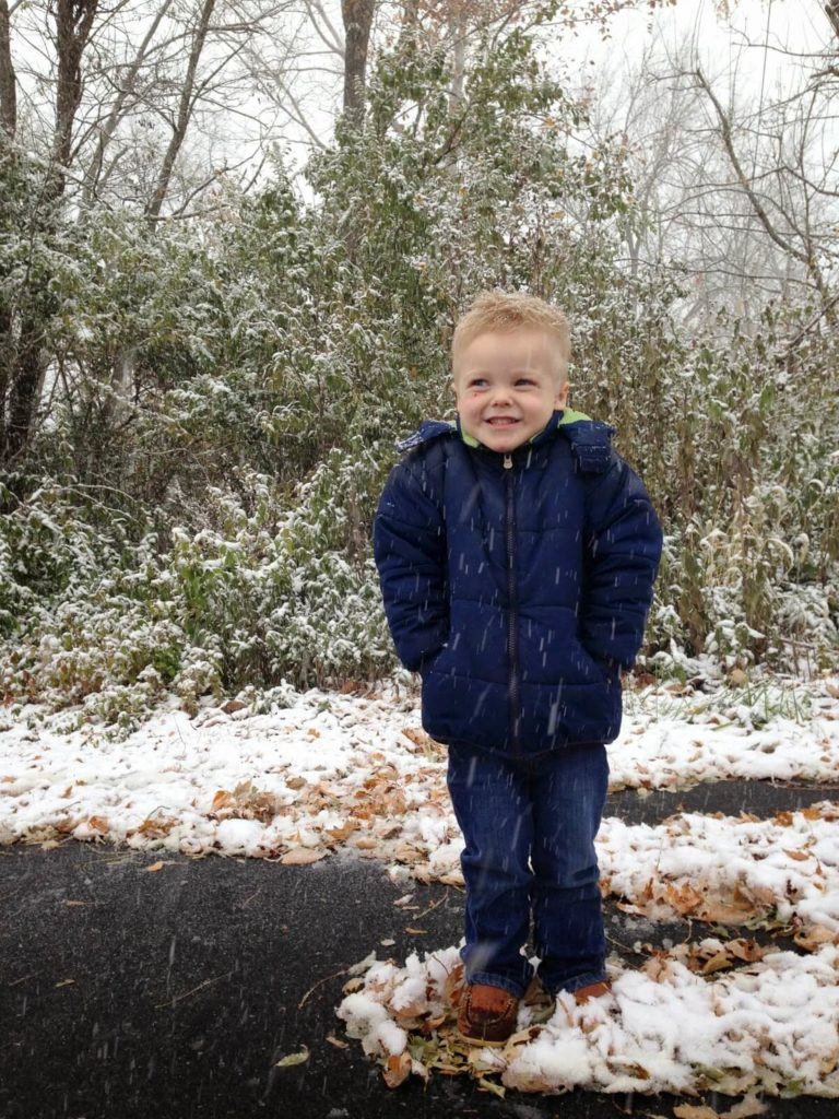 boy standing in snowfall