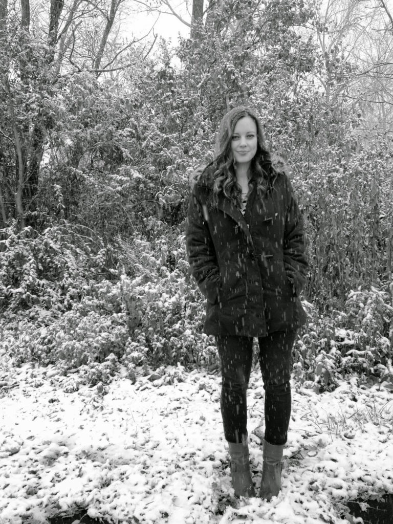 young woman standing in snow fall