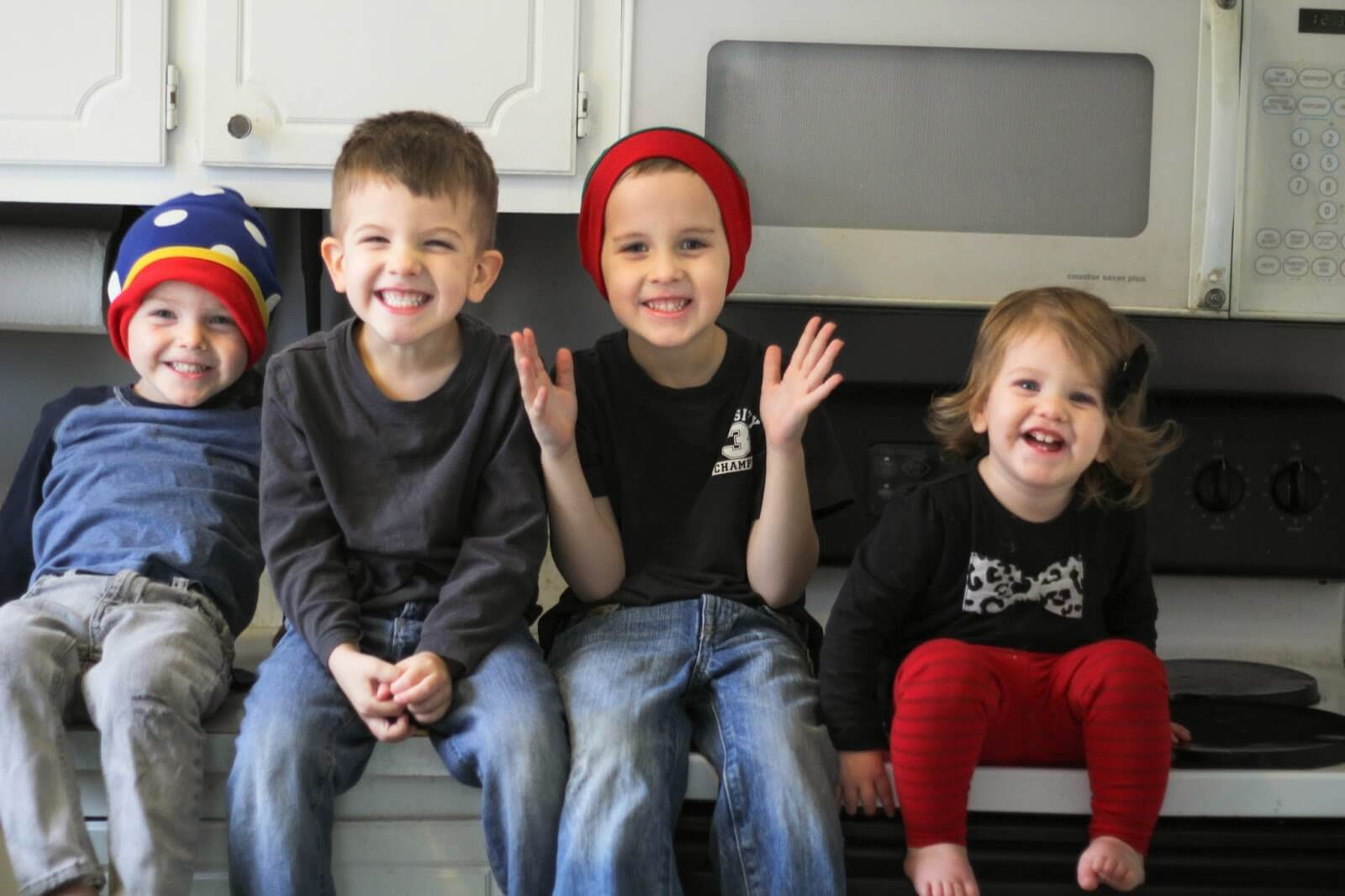 4 kids sitting on counter