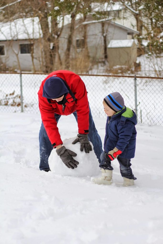 dad and son making snowman