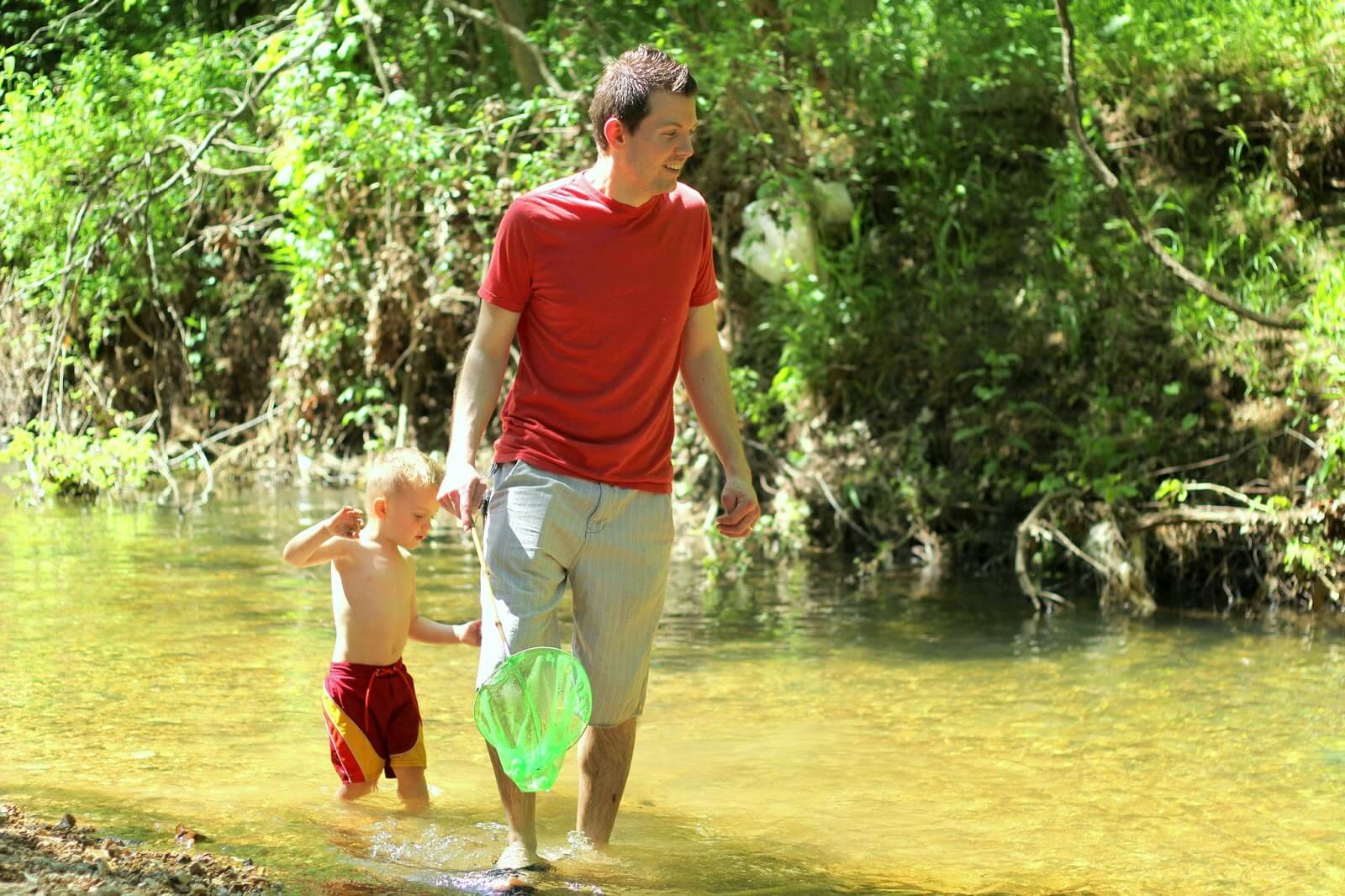 dad and son in creek