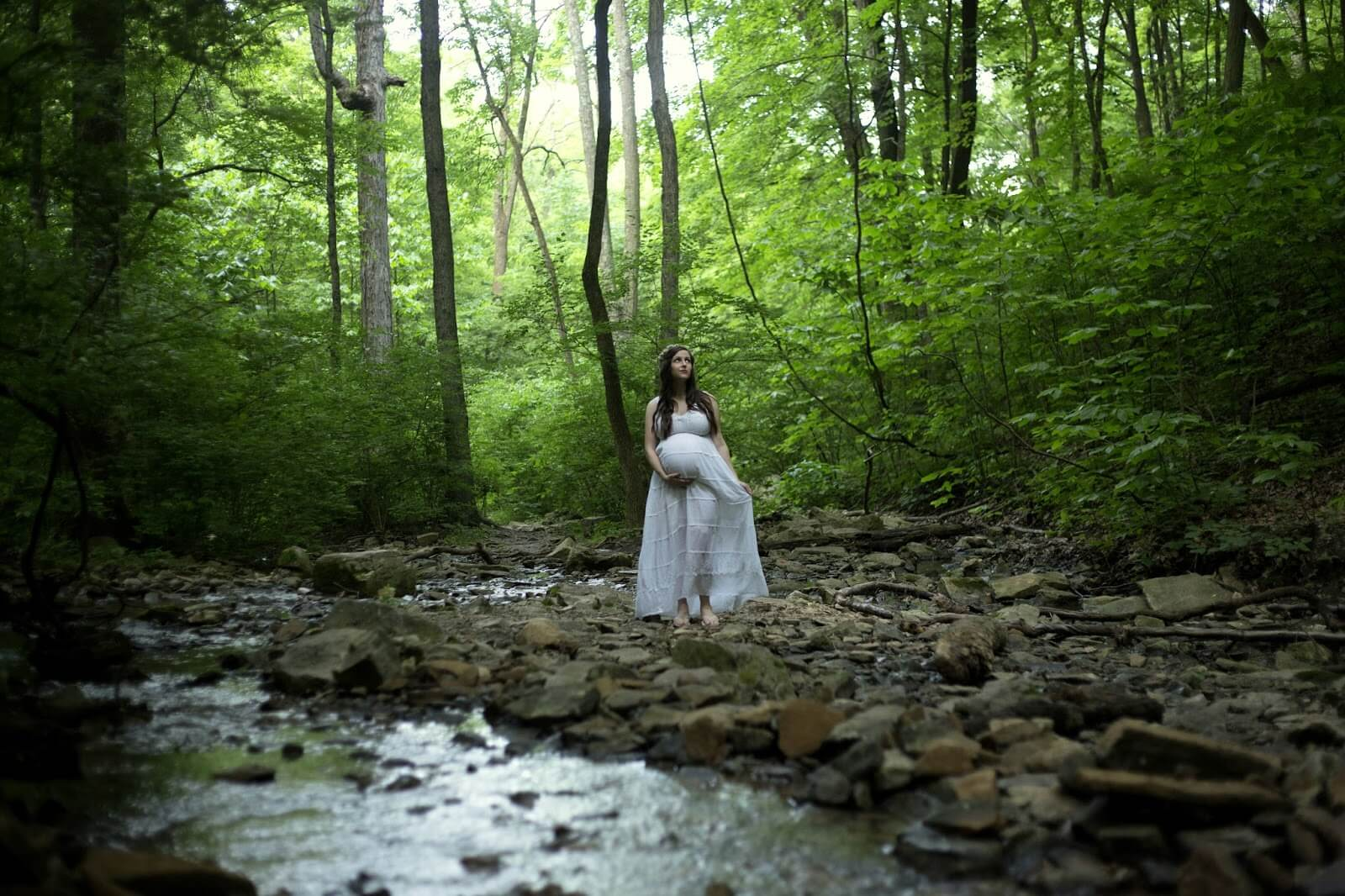 woman in white dress in forest by stream