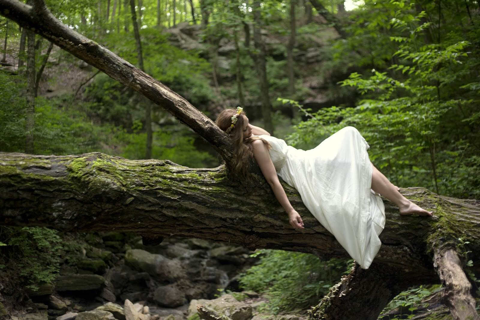 girl posing on fallen log