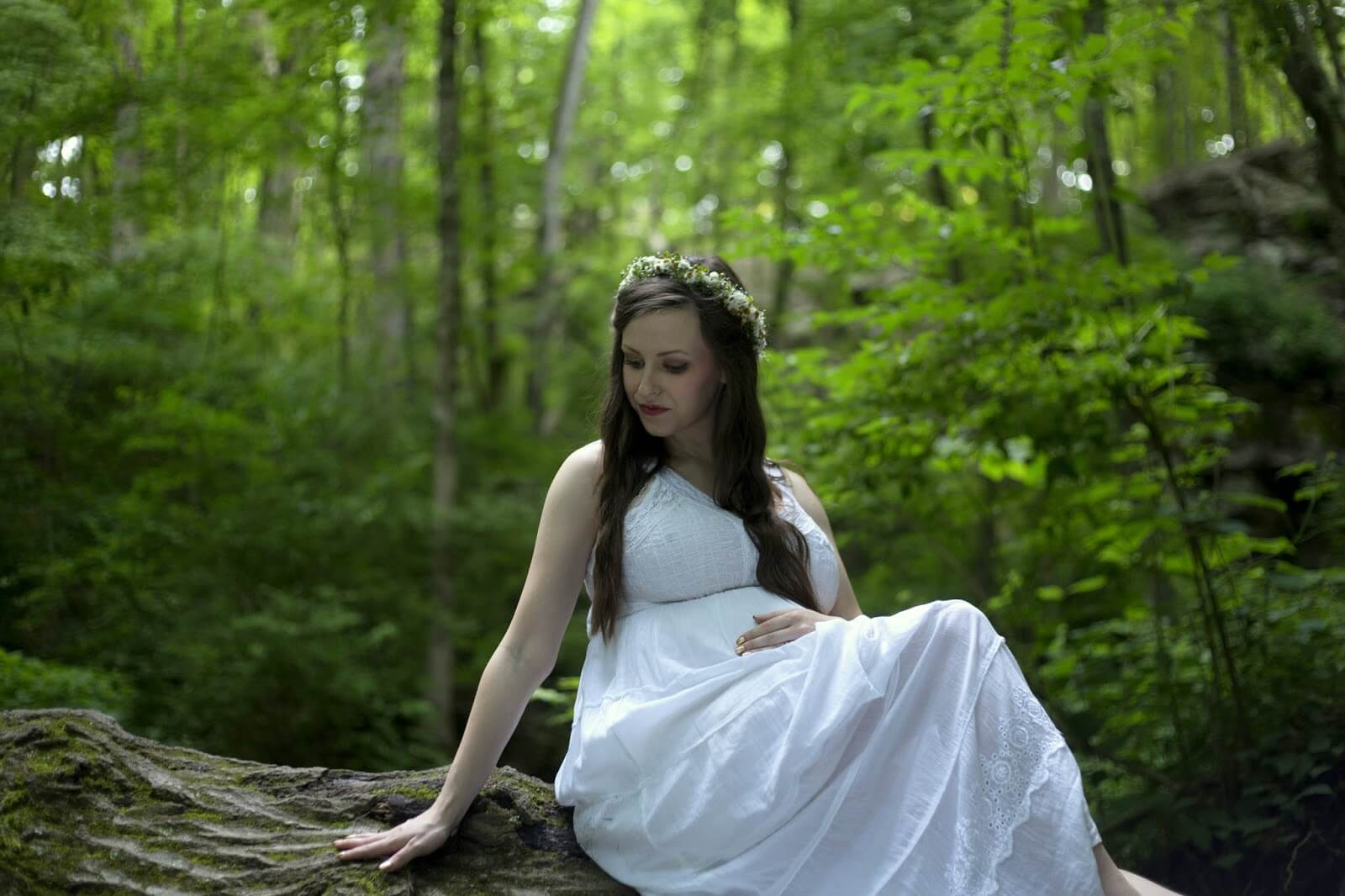 pregnant girl in white dress sitting on fallen tree