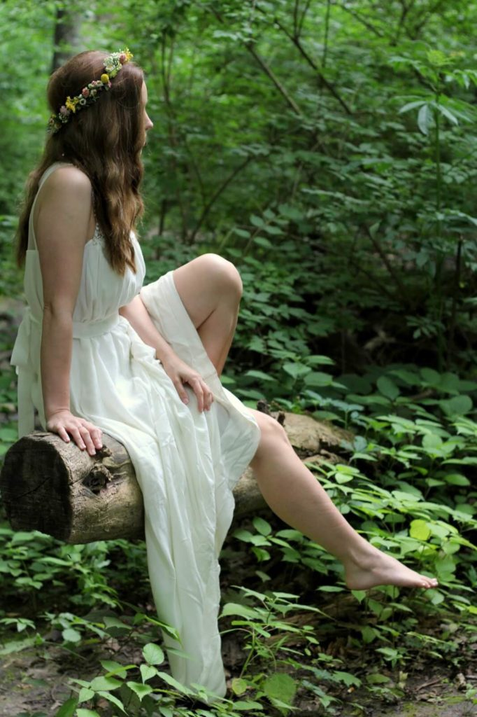 girl in white dress sitting on fallen log