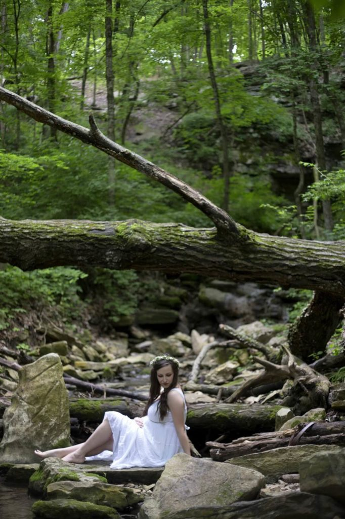 girl sitting on rocks in white dress