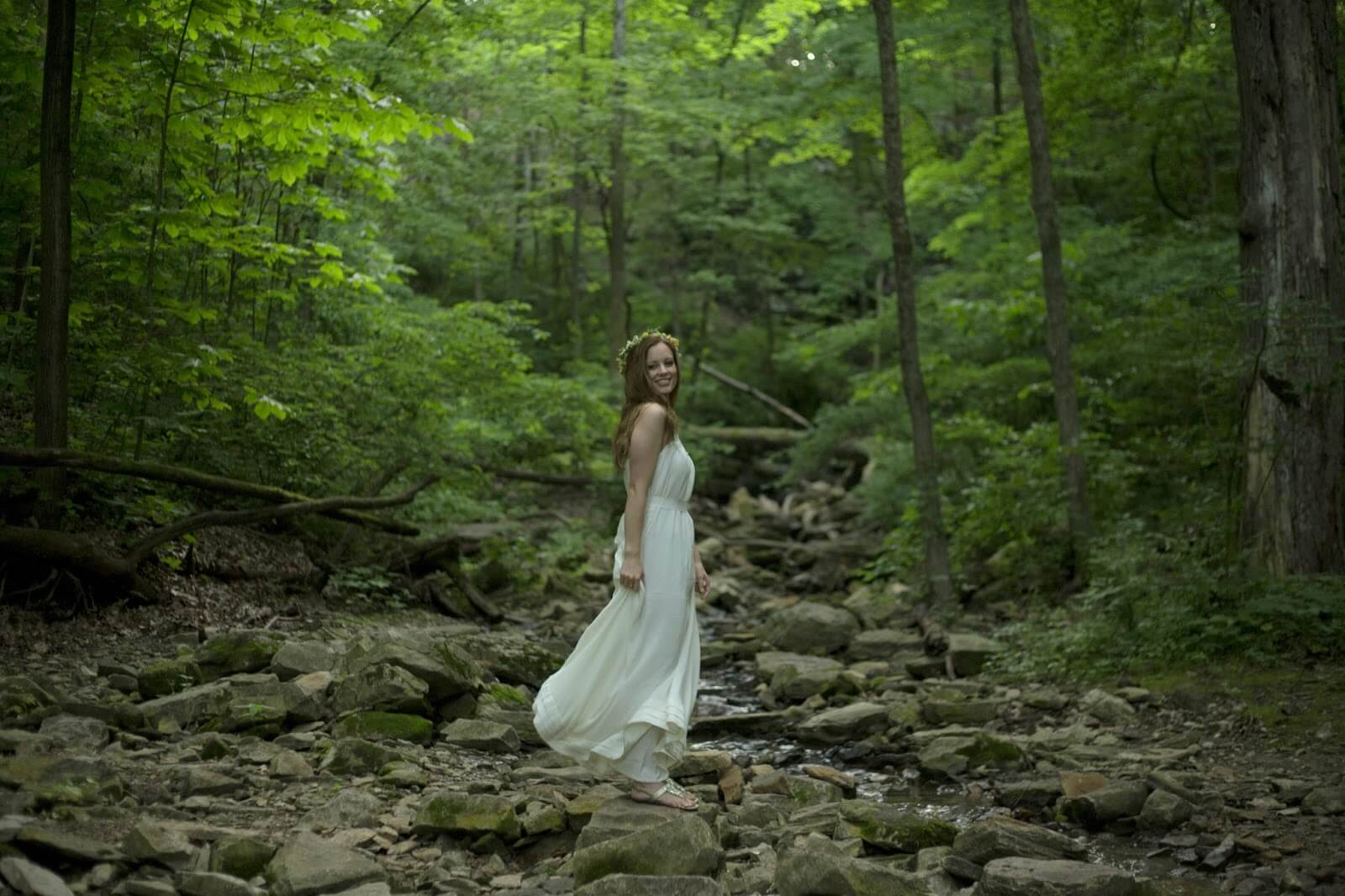 zoomed out shot of girl in white dress in forest