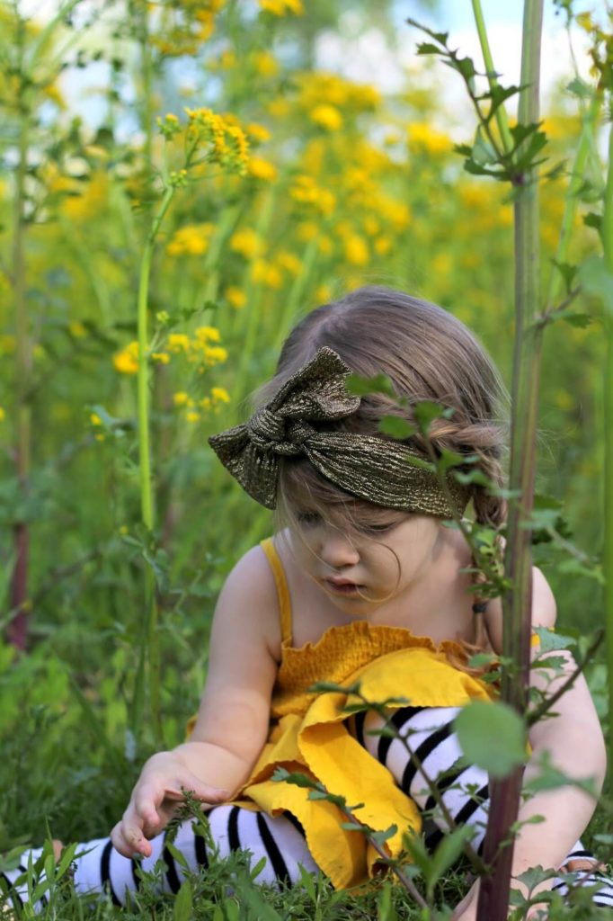 young girl in yellow dress in yellow flowers