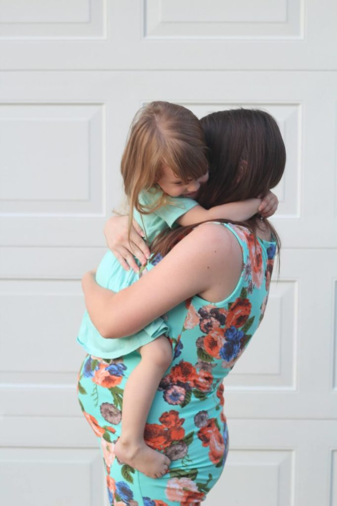 toddler girl hugging mom